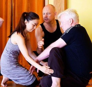 Tutor Daizan guides two students learning how to adjust a posture on the Zenways yoga teacher training