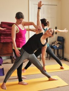 Trikonasana adjustment on the zenways yoga teacher training course
